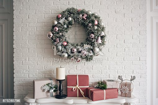 a traditional bright christmas wreath hanging over the fireplace on a white brick wall and. Black Bedroom Furniture Sets. Home Design Ideas