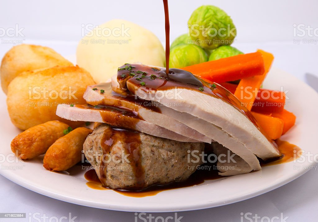 traditional british christmas dinner with sauce being poured royalty free stock photo