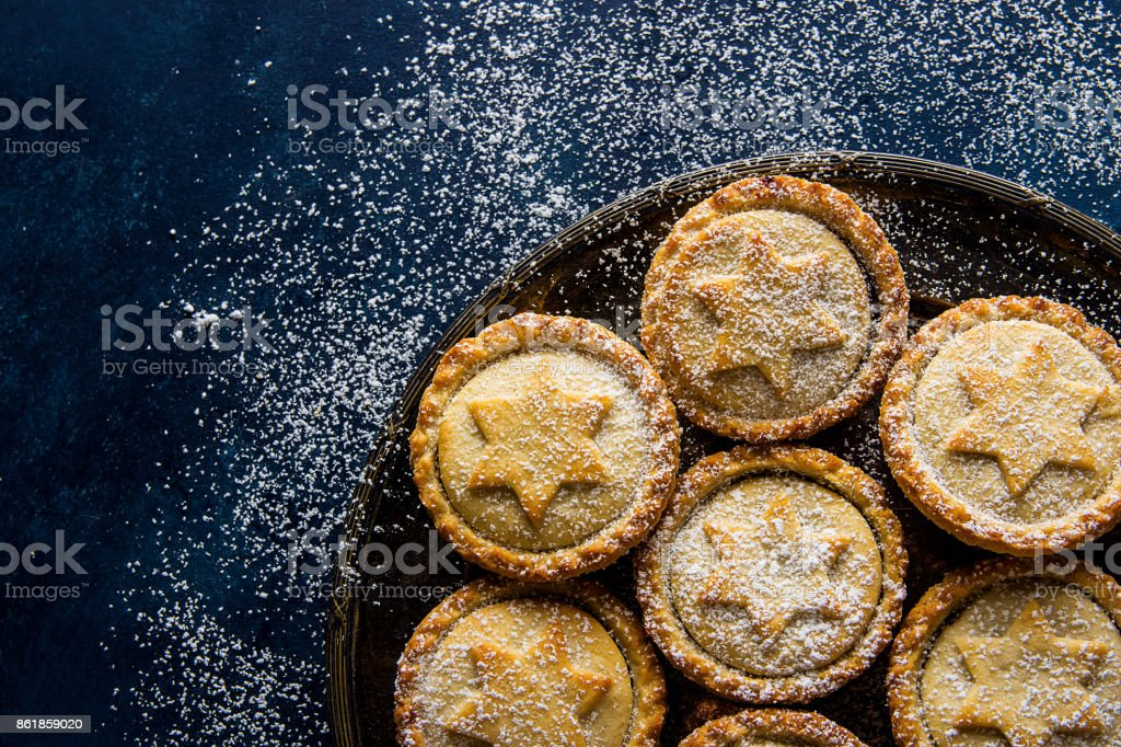 Traditional British Christmas Pastry Dessert Home Baked Mince Pies with Apple Raisins Nuts Filling Golden Shortcrust Powdered on Vintage Metal Plate Dark Blue Snowy Background Top View Copy Space stock photo