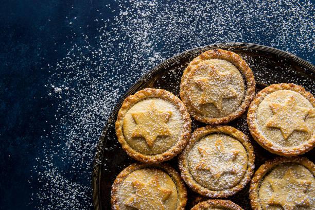 Traditionelle hausgemachtes britische Weihnachten Gebäck Dessert Mince Pies mit Apfel-Rosinen-Nüssen füllen goldene Mürbeteig Puderzucker auf Vintage Metallplatte verschneiten dunkelblauem Draufsicht Textfreiraum – Foto
