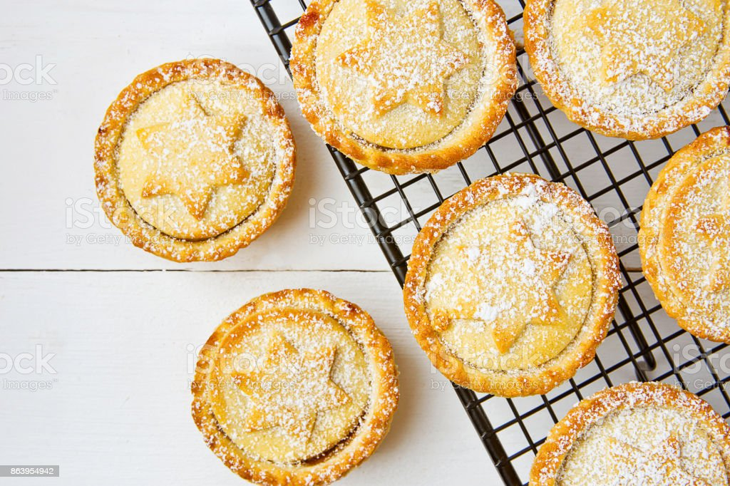 Traditional British Christmas Pastry Dessert Home Baked Mince Pies with Apple Raisins Nuts Filling on Cooling Rack. Golden Shortcrust Powdered. White Plank Wood Table. Festive Setting stock photo