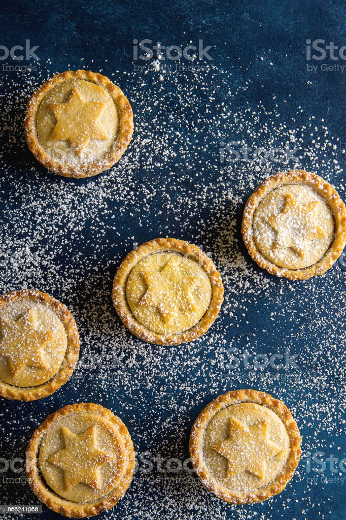 Traditional British Christmas Pastry Home Baked Mince Pies with Apple Raisins Nuts Filling Scattered on Ice Sugar Dusted Dark Blue Background. Golden Shortcrust Powdered Top View Copy Space stock photo