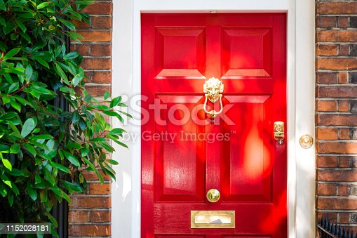 Color image depicting the exterior of a building on a traditional city street in Belgravia, an affluent area of London, UK. The house has a pretty red door, red brick walls, and the facade is decorated with a lush, verdant green bush. Room for copy space.