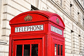 Low angle view of traditional old style UK red telephone box isolated against a building background