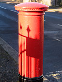 Traditional British red post box. Victorian cast iron fence is casting the shadow.