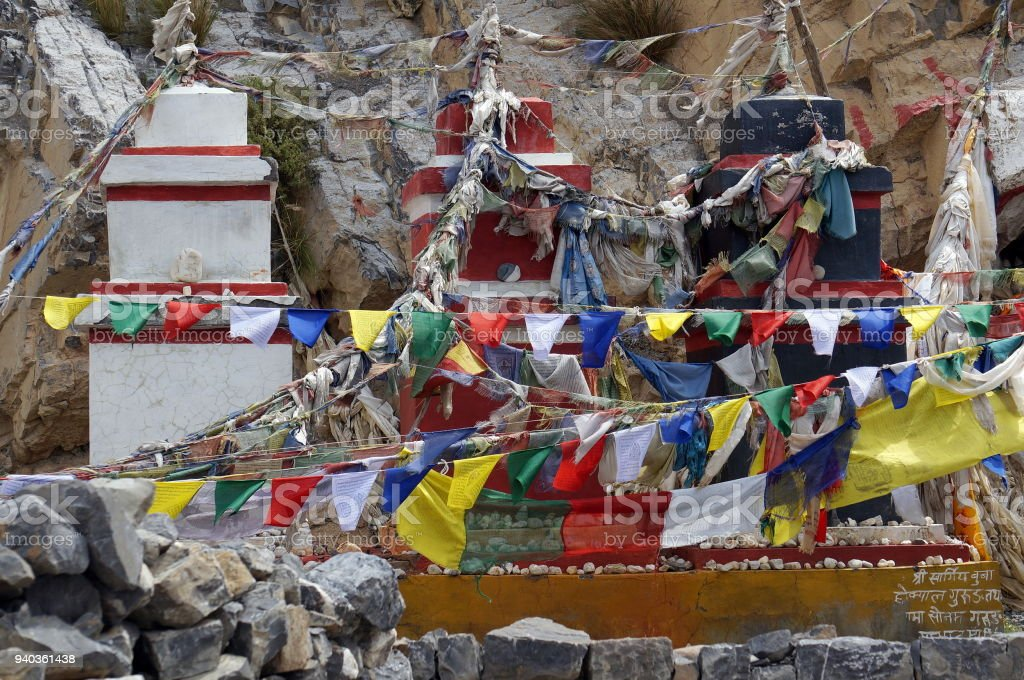Traditional Buddhist chortens stand in the Himalayan mountains in the place of worship of the gods, with garlands of flags. stock photo