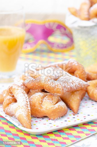 Homemade New Orleans style beignets are small squares of fried dough covered in powdered sugar prepared for Mardi gras. Served on a plate with a glass of orange juice ,colored paper napkin, confetti and colombina carnaval mask in the background