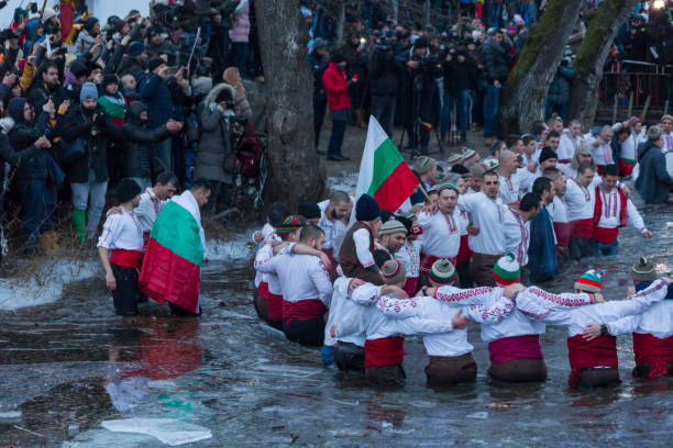 Traditional bulgarian ritual dance in the cold icy river stock photo