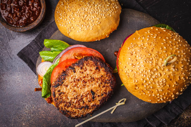Traditional burgers with meat, sauce and vegetables on dark background, top view. stock photo
