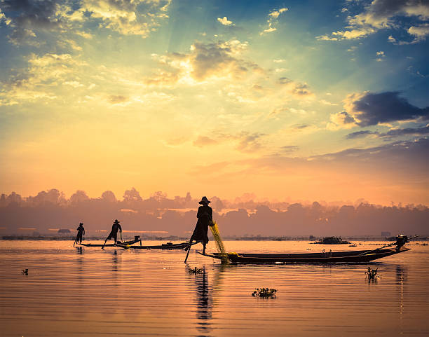 Traditional Burmese fishermen at Inle lake Myanmar Myanmar travel attraction landmark - traditional Burmese fishermen sihouettes at Inle lake on sunset, Myanmar famous for their distinctive one legged rowing style myanmar stock pictures, royalty-free photos & images