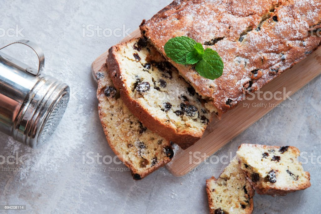 Traditional cake with raisins sprinkled with powdered sugar and mint leaves decorated. At Marble gray background stock photo