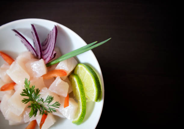 Traditional Ceviche bowl with white fish. Top view on dark background with copy space. stock photo