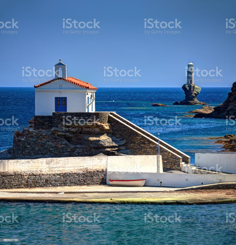 Traditional chapel of Panagia Thalassini and Lighthouse Tourlitis in Andros island, Cyclades, Greece stock photo