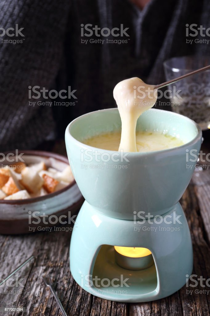 Traditional cheese fondue with baguette and white wine stock photo