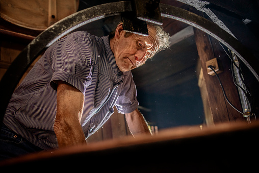 Senior male cheesemaker at work over a huge cauldron, making artisanal cheese in the traditional way, in a log cabin in the Swiss Alps, Bernese Oberland region of Switzerland.