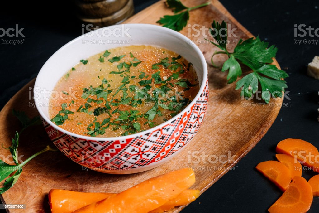 traditional chicken soup in bowl and wooden board stock photo