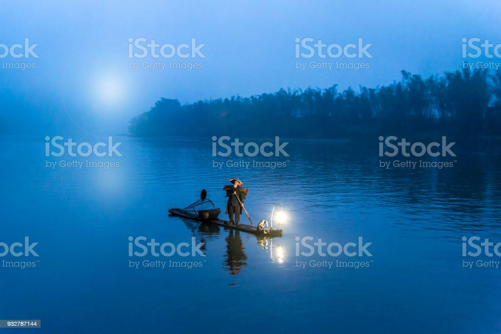 Traditional Chinese 75 year old senior fisherman in traditional clothes and bamboo hat on his wooden fishing raft with two cormorants fishing on the Li River in the early morning fog light at sunrise. Shot at Xing Ping, close to the city of Yangshuo Count stock photo
