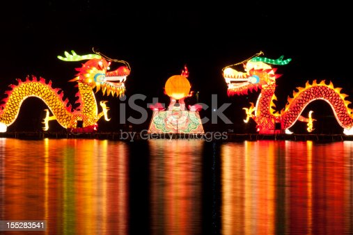 Traditional Chinese dragon lights for Chinese new year. Two dragons are playing with a pearl in the lake, isolated on black ground.