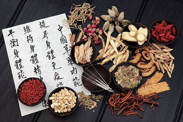 Traditional Chinese Medicine Acupuncture needles with chinese herbal medicine selection and mandarin calligraphy script on rice paper describing the medicinal functions to maintain body and spirit health and balance body energy. chinese herbal medicine stock pictures, royalty-free photos & images