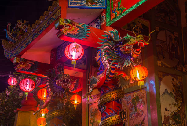 Traditional Chinese Temple with dragons and lights on columns in the night on koh Samui stock photo