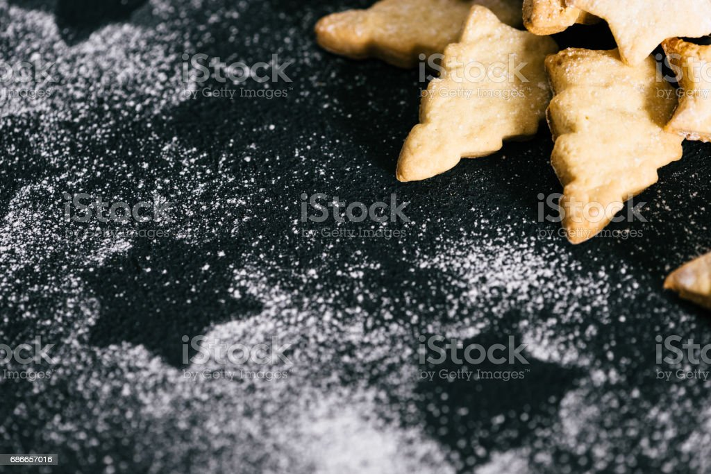 Traditional Christmas cookies powdered with sugar on black table royalty-free stock photo