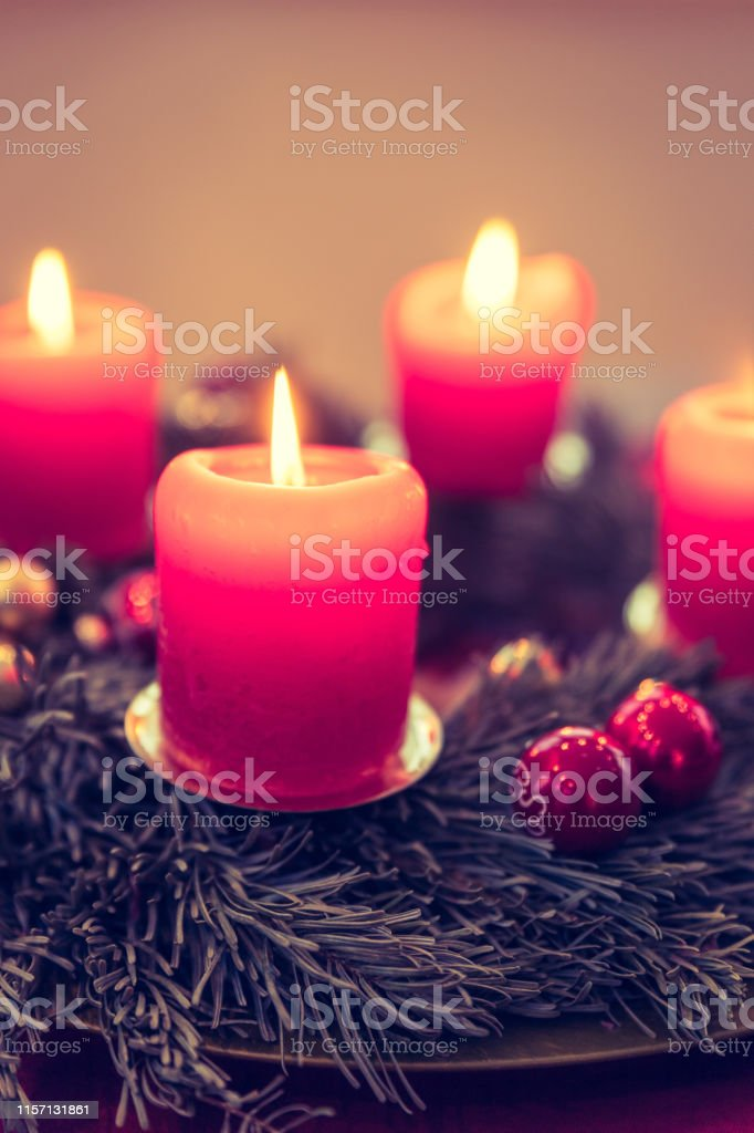 Close up of advent wreath with red lights and flame, fir branches