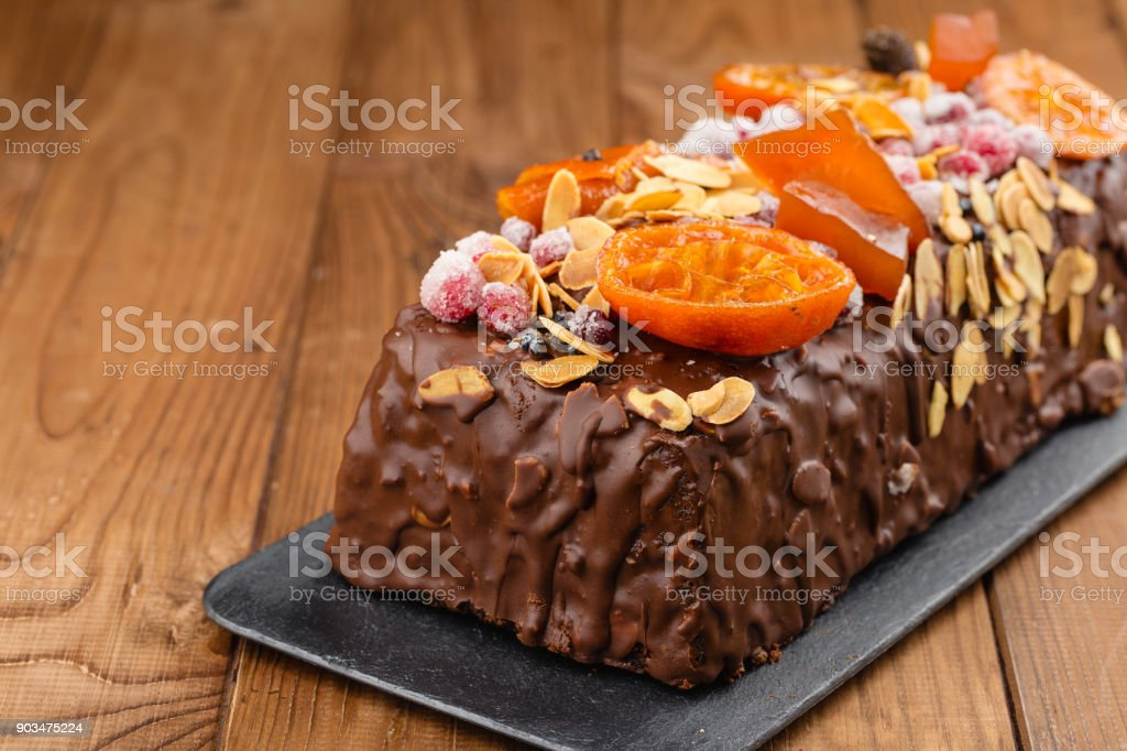 Traditional christmas fruit cake in chocolate glaze on wooden background stock photo
