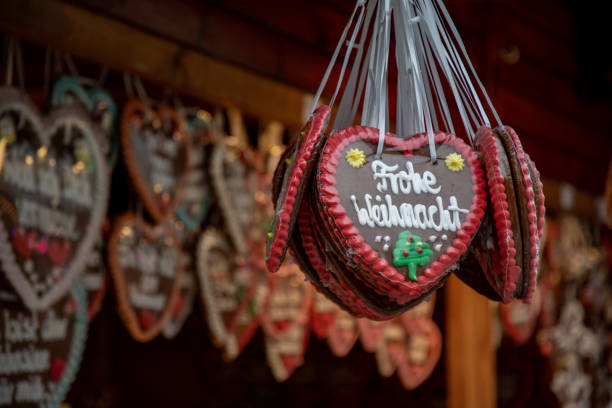 """Traditional Christmas gingerbread cookies with inscription """"Merry Christmas"""" in German language. Bunch of colorful ornate gingerbread pastries closeup on blurry background of Christmas fair market stock photo"""