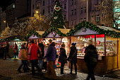 Prague: People passing by illuminated kiosks with souvenirs and decorations during traditional Christmas market taking place each year on December. It is very popular destination with tourists visiting Prague.