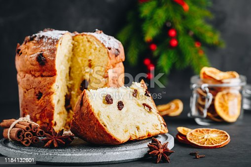 istock Traditional Christmas Panettone cake with dried fruits on dark stone background 1184132601