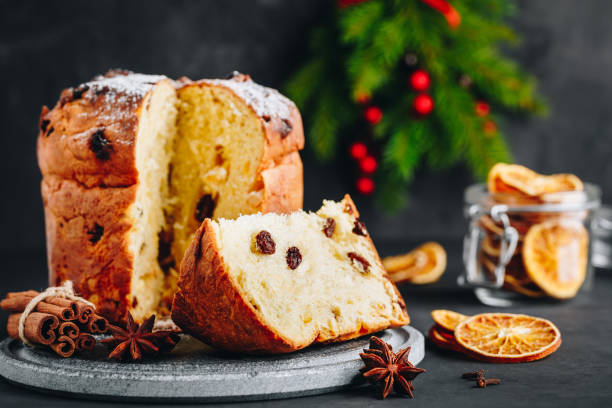 traditional christmas panettone cake with dried fruits on dark stone background - panettone foto e immagini stock