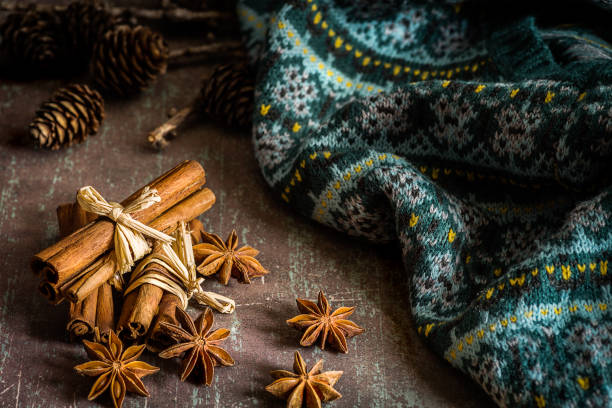 Traditional Christmas spices (star anise, cinnamon sticks for festivity) and warm knitwear on rustic background - foto stock