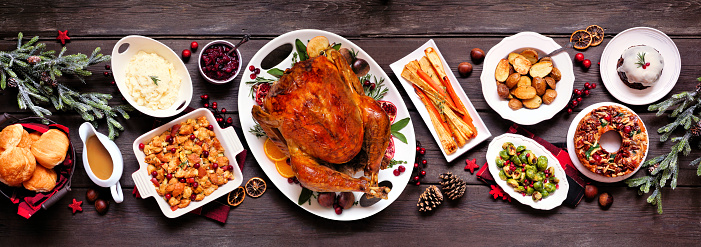Traditional Christmas turkey dinner. Top view panoramic table scene on a dark wood banner background. Turkey, potatoes and sides, dressing, fruit cake and plum pudding.