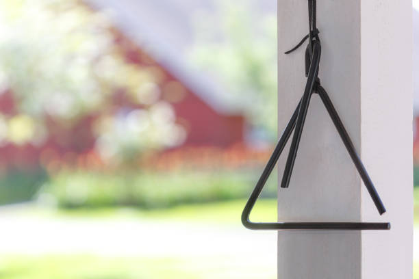 Traditional classic dinner bell on porch near big red barn, copy space, no people, background image for announcements, meals, dinners, posters stock photo
