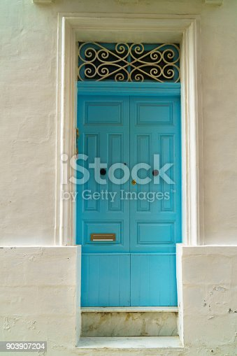 istock Traditional classic style old wooden medieval vintage blue painted door with knockers in Valletta, Malta. 903907204