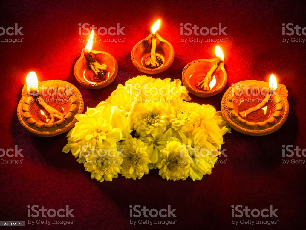 Traditional clay diya lamps lit with flowers for Diwali festival celebration. royalty-free stock photo