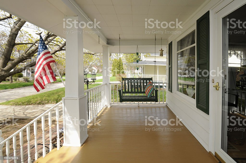 Traditional Clean Family Residential House, Covered Porch, Swing, USA Flag stock photo