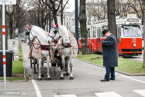 Vienna, Austria, 23 March 2017: Traditional Coachman and two white decorated horses, called Fiaker, waiting for tourists at central street of Vienna, Austria.