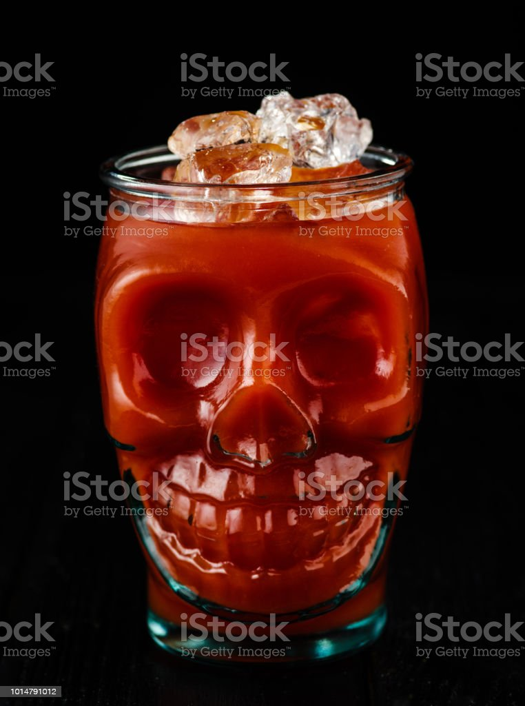 Traditional cocktail Bloody Mary with ice in a skull glass on black table. стоковое фото