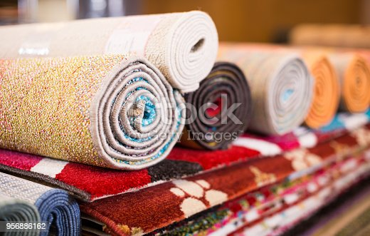 Stack of traditional  colorful carpets in carpet shop, nobody