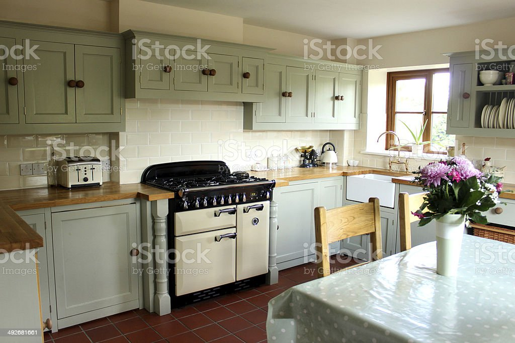 Traditional country kitchen, gas range cooker, wooden worktops, table, chairs stock photo