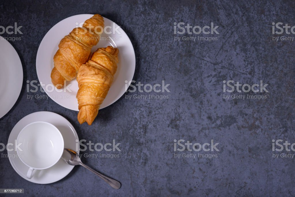Traditional croissants and empty cup for tea or coffee stock photo