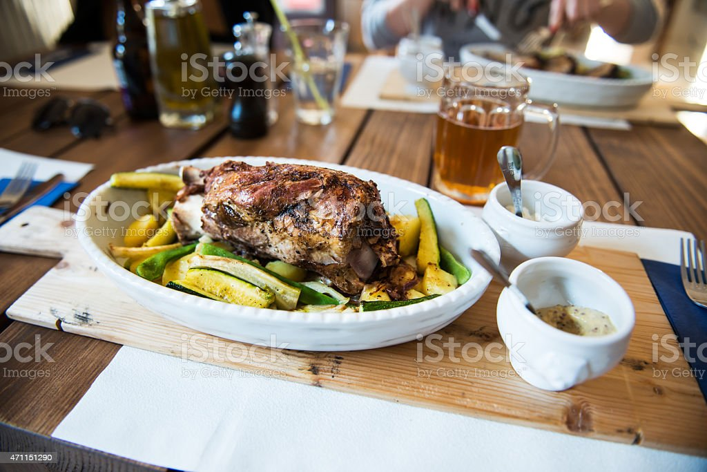 Traditional czech dinner with roasted pork leg and bee stock photo