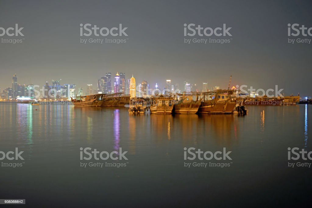 Traditional Dhows in front of nightly Doha Skyline stock photo