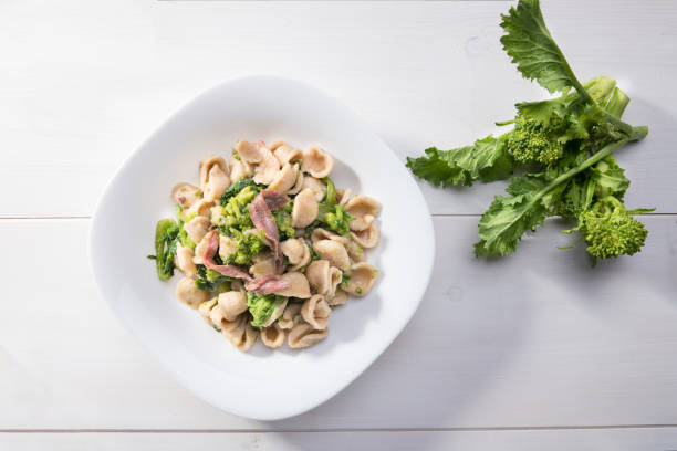 Traditional dish of Apulia region pasta Orecchiette with turnip greens and salted anchovies, top view, white wooden background Vegetarian wholegrain Italian pasta, a traditional dish in Puglia, southern Italy, orecchiette with turnip greens and salted anchovies, top view white, wooden background brassica rapa stock pictures, royalty-free photos & images