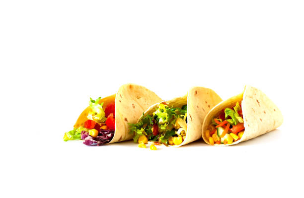 Traditional dish of Mexican cuisine. Corn tortilla tacos with vegetable filling on isolated white background. Traditional dish of Mexican cuisine. Corn tortilla tacos with vegetable filling on isolated white background. Closeup, copy space. taco stock pictures, royalty-free photos & images