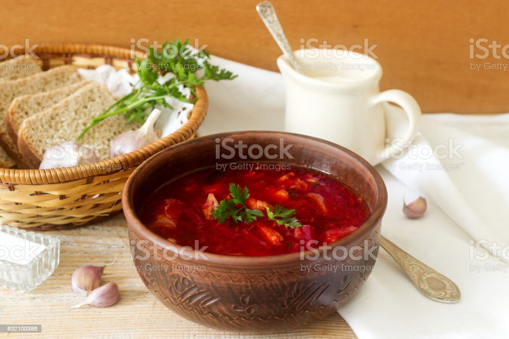 A traditional dish of Russian and Ukrainian cuisine - borsch. Soup with beets, meat, potatoes and beans. Served with sour cream and garlic. stock photo