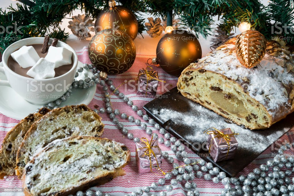 traditional Dutch and German kerststol, as Christmas bread, hot chocolate, with golden  holiday decorations, stock photo