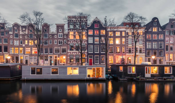 Traditional Dutch buildings and houseboats along the canals of Amsterdam, Netherlands stock photo
