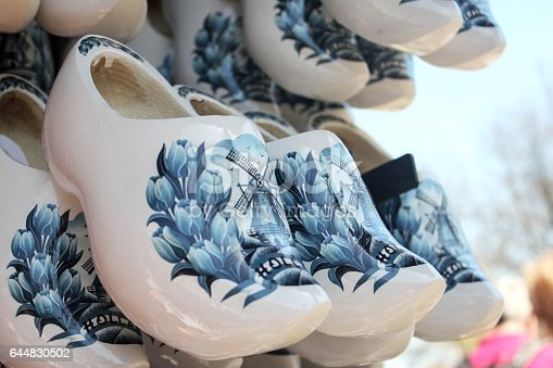White Dutch clogs souvenir hanging on the retail display to be sell. There's a painted image of windmill and tulip with a holland text on the shoe.